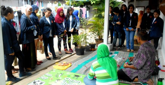 Beberapa Mahasiswi STHB berdiri mengelilingi Yanti seorang pengrajin yang bekerjasama dengan Lapas Yogyakarta dalam pembinaan keterampilan kepada WBP Wanita, di Blok Wanita Lapas Yogyakarta pada Sabtu (09/11).